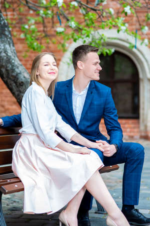 Smiling Happy Caucasian Couple Sitting on Bench in Cosy Yard Outdoors. Vertical Shot