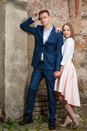 Elegant Fashionable Caucasian Couple Posing Embraced Together Outdoors. Vertical Image Composition