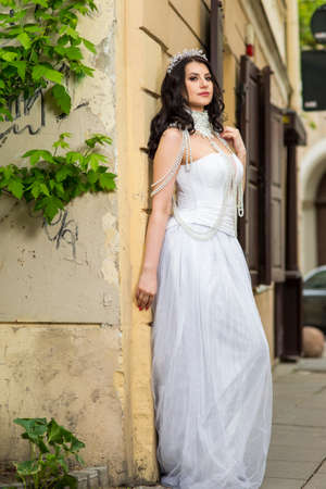 Portrait of Caucasian Brunette Bride with Tiara Posing Against Old Building. Wearing Beads Necklace and Decorations. Vertical Composition