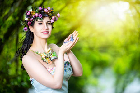 Fantastic Portrait of Sensual Brunette Female in White Dress Outdoors. Posing with Flowery Chaplet and Butterfly Against Sunlight. Horizontal image Composition