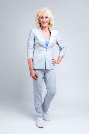 Stilvolle reife kaukasische blonde Frau im modischen Anzug posiert vor weißem Hintergrund im Studio.Vertical image