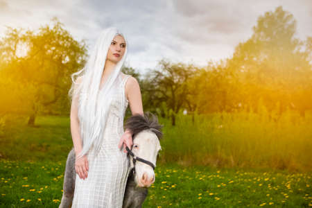 Blond Woman with Long White Hair Posing with  pony Horse Against Sunlight Outdoors. Horizontal Image