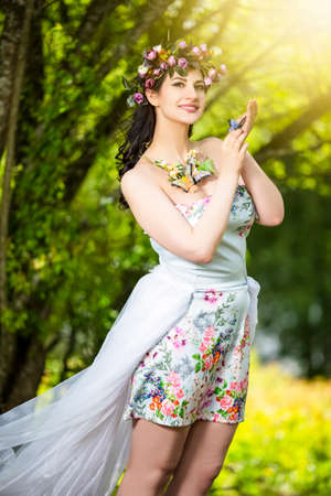 Fantastic Portrait Positive Sensual Brunette Female in White Dress Outdoors. Posing with Flowery Chaplet and Butterfly Against Sunlight.Vertical Image Orientation