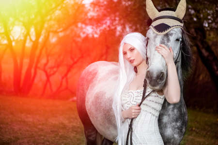 Beautiful Caucasian Blond Female with long Hair Standing with Grey Horse Against Bright Light on The Background. Horizontal Image