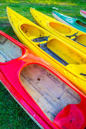 Five Colorful Plastic Kayaks Placed Together For Drying on Grass Outdoors. Vertical Image 写真素材