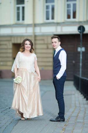 Glückliches, gerade verheiratetes Paar, das einen Spaziergang im Freien macht. Vertikales Bild