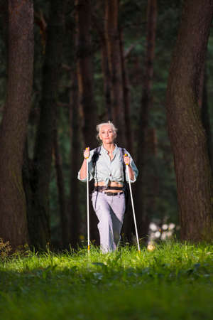 Seniors Sports and Healthy Lifestyle Concepts. Mature Caucasian Woman Having Fitness Nordic Walking Exercise with Backpack in Deep Forest. Vertical Image