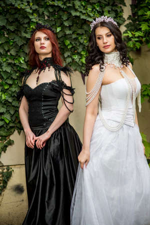 Two Caucasian Models Posing Together Outdoors. Standing in Black and White Dresses. Wearing Tiara.Vertical image Orientation