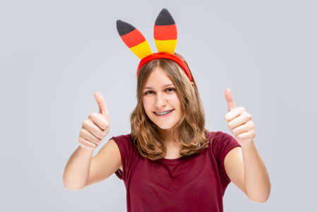 Teenage Lifestyle Concepts. Caucasian teenage Girl Posing With Hoop Demonstrating German Flag. Showing Thumbs Up Sign and Smiling. Horizontal image