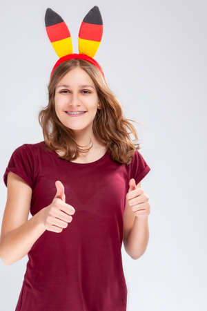Teenage Lifestyle Concepts. Caucasian teenage Girl Posing With Hoop Demonstrating German Flag. Showing Thumbs Up Sign and Smiling. Vertical Image