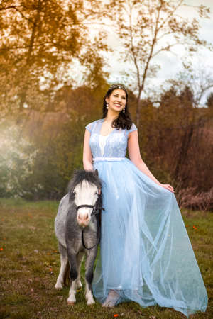 Portrait of Smiling Caucasian Brunette in Long Blue Dress Posing With Pony Horse Against Bright Colorful Light. Vertical Image