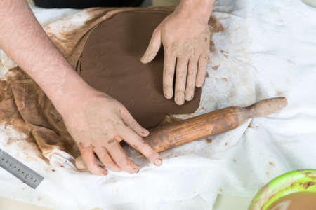 Pottering Ideas and Concepts. Closeup of Hands of Male Worker Rolling a Piece of Wet Clay on Table Before Moulding.Horizontal Composition Stockfoto
