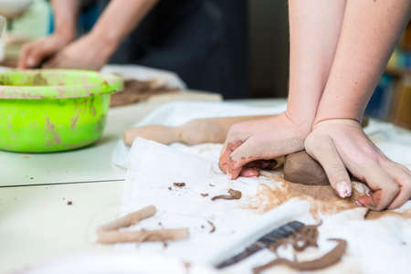 Pottering Concepts. Closeup of Hands of Female Worker Rolling a Piece of Wet Clay on Table Before Moulding.Horizontal Image Stockfoto