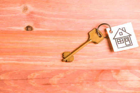 Family and Home Concepts. House Symbol Along With Golden Key Over Vintage Wooden Background. Horizontal Image