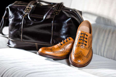 Closeup of Pair of Male Full Brogued Tan Oxford Shoes Placed With leather Men's Bag On Pale Sofa Indoors.Horizontal Shot Stock Photo