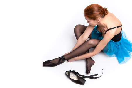Portrait of Sensual Caucasian Female Ballet Dancer Making up Pointes Shoes With Laces. Horizontal Image