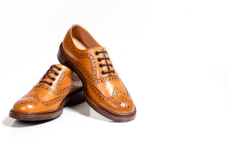Footwear Concepts. Full Broggued Tan Leather Oxfords Shoes Isolated On White Background. Horizontal Image Orientation