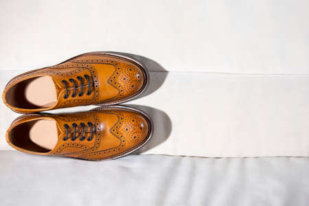 Footwear Concepts. Closeup of Full Broggued Tan Leather Oxfords Shoes Ion Pale Color Sofa. Placed Together. Horizontal Orientation Zdjęcie Seryjne
