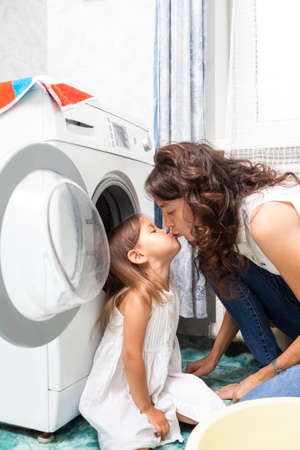 Family Helpers Concepts. Mother and Her Little Daughter Kissing whilst Doing Linen Washing in Bathroom. Vertical image