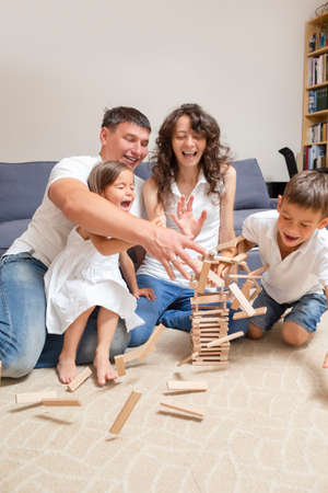 Family Values. Emotional Happy Caucasian Couple Teaming Up with Children While Demolishing Tower of Wooden Tiles Indoors. Vertical Shot