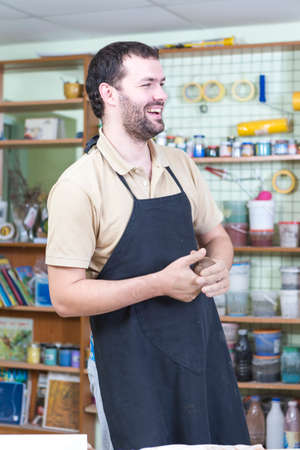 Male Ceramist In Workshop. During a Working Process. Having Laugh and Holding A Piece of Clay. Vertical Image Composition