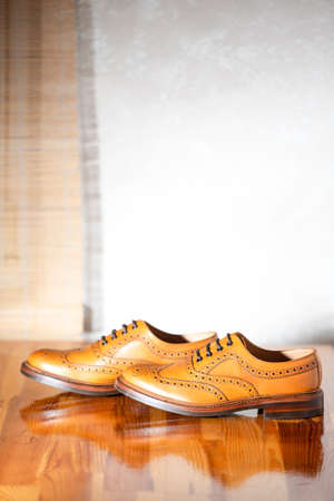 Pair of Male Full Brogued Tan Oxford Shoes. Placed Together on Laqured Table Indoors. Vertical Image Composirion