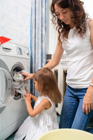 Family Helpers Concepts. Mother and Her Little Daughter Doing Linen Washing in Bathroom. Vertical image Orientation
