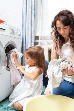 Family Helpers Concepts. Mother and Her Little Daughter Doing Linen Washing. Vertical image Stockfoto