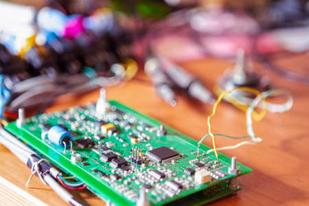 Electronics Ideas. Automotive Printed Circuit Board with Surface Mounted Components and Connected Wire Probes During a Process of Tesing  in Laboratory. Horizontal Image Composition