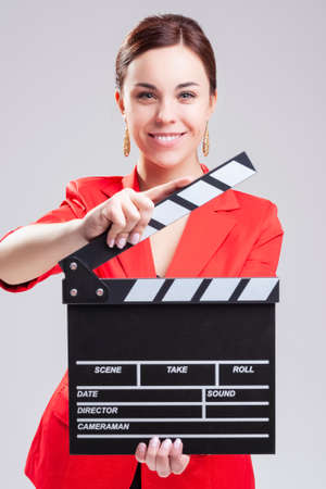 Smiling Caucasian Female Posing in Red Blazer with Actioncut Indoors. Focus on Models Face. Vertical Image Stockfoto