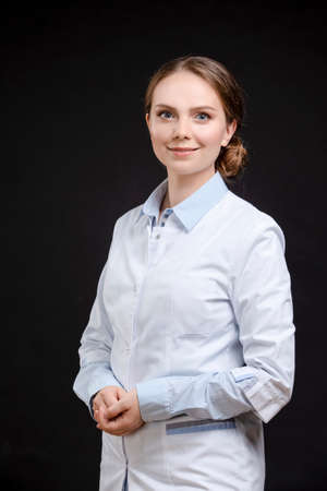 Portrait of Professional Female GP Doctor Posing in Doctor's Smock Against Black. Vertical image