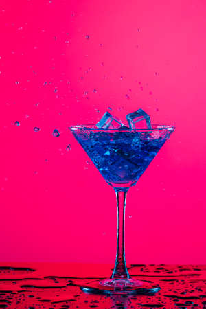 Drink Spilling Out of The Glass Goblet with Icecubes and Colorful Liquid. Over Colorful Background. Vertical Shot