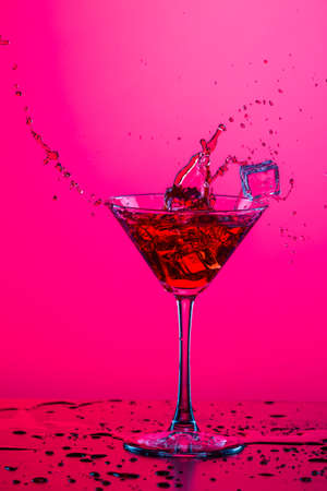 Droplets of Drink Spilling Out of The High Glass Goblet with Ice Cubes and Colorful Liquid. Isolated On Colorful Background. Vertical Image Stock Photo