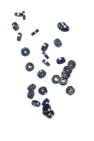 Large Amount of Ball Bearings Shaped and Formed In Free Fall Bulk. Isolated Over White Background. Vertical Image Composition