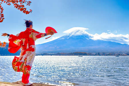 Asian Woman In Traditional Japanese Kimono With Fan Posing at Fuji Mountain at Kawaguchiko Lake in Japan. Horizontal image