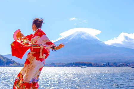 Asian Woman In Traditional Japanese Kimono And Fan Posing at Fuji Mountain at Kawaguchiko Lake in Japan. Horizontal Orientation Image