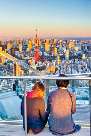 Romantic Young Couple Sitting Together on Top of Tokyo Scyscraper and Enjoying the City View with Tokyo Tower in Background During Blue Hour. Vertical Image