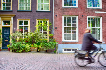Woman Passing on Conventional Dutch Bicycles Against Classic Red House with Lots of Flowers on the Background. Blurred Motion. Horizontal Image