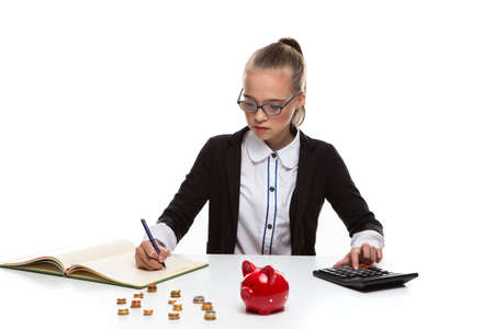 Money Saving Concepts. Teenager Blond Girl Posing With Coins and Moneybox. Calculating Income With Calculator For Savings.Horizontal Image
