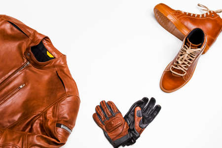 Motorcyclist Concepts. Set of Protective Motorcycling Clothing Consisting of Leather Jacket, Leather Tan Boots and Stitched Gloves. Horizontal image Stock Photo