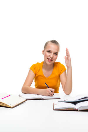 Educational Ideas. Portrait of Smiling Caucasian Teenager Girl Posing with Books and Lifted Hand. Isolated On White. Vertical Image