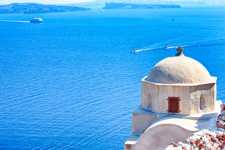 Segelboote in der Nähe der vulkanischen Hänge der Caldera von Santorini Oia oder Ia Village in Griechenland. Mit traditioneller blasser Kuppel-orthodoxer griechischer Kirche im Vordergrund. Horizontales Bild
