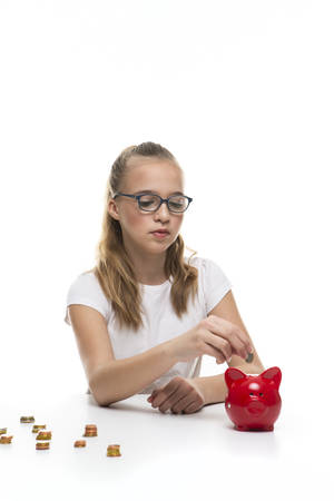 Money Saving Concepts. Teenager Blond Girl Posing With Coins and Using Moneybox for Laying Up Money. Vertical image Standard-Bild