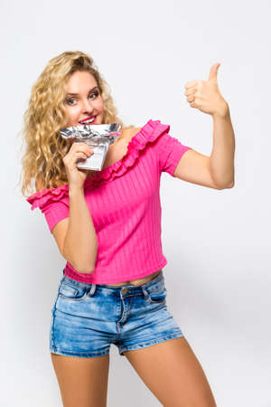 Food Concepts. Portrait of Positive Tranquil Caucasian Blond Female With Bar of Chocolate.Showing Thumbs Up Sign. Posing on White. Vertical Image