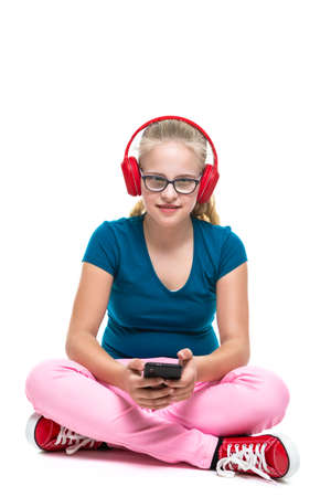 Teenager Lifestyle. Portrait of Positive Caucasian Teenager Girl With Red Headphones And Listening To Music with Smartphone. Posing Against White. Vertical Shot 스톡 콘텐츠