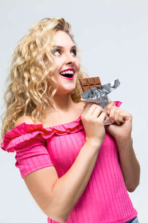 Food Concepts. Portrait of Cute Alluring Caucasian Blond Female Eating Chocolate Bar. Posing on White. Vertical image