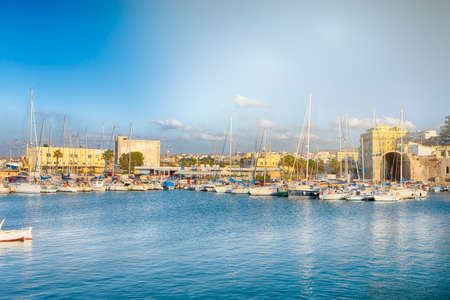 Greek Travel Concepts. Old Venetian Harbour of Heraklion City on Crete with line of Fisihing Boats and Yachts in the Foregound At Daytime. Horizontal Image Composition