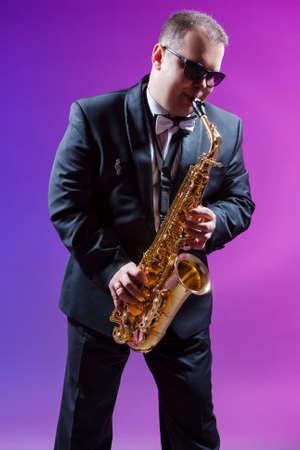 Musicians Concepts. Portrait of Expressive Caucasian Saxophonist Against Colorful Background. Vertical Compostiion