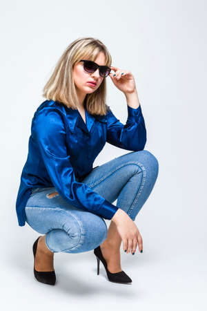 Youth Lifestyles. Portrait of Alluring Caucasian Blond Girl Posing in Sunglasses in Blue Clothing Against White. Vertical image