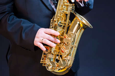 Closeup of hands of Professional Saxophonist Player Against Black. Horizontal image